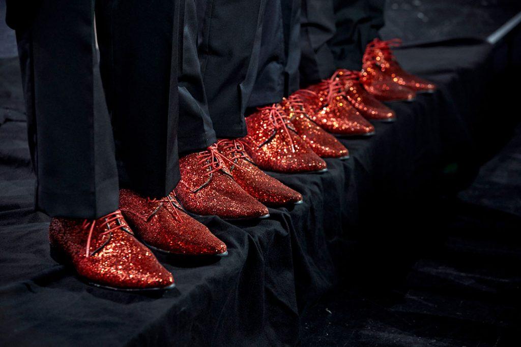 Röda glittriga skor på svart golv
